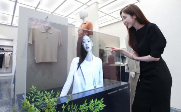 ▲서울 마포구에 위치한 '무신사 스탠다드 홍대'에서 LG디스플레이 모델이 투명 OLED로 신상 의류를 확인하고 있다. (사진제공=LG디스플레이)