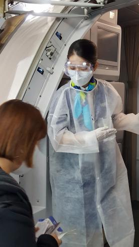 ▲에어부산 기내 승무원이 방호복 및 고글을 착용한 상태로 승객을 안내하고 있다.  (사진제공=에어부산)