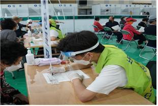 ▲노원구 예방접종센터에서 예진표 작성을 지원하는 자원봉사자. (사진제공=서울시)