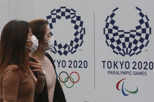 ▲일본 여성들이 16일 도쿄올림픽 로고와 올림픽 상징인 오륜기가 그려진 포스터 앞을 지나고 있다. 도쿄/AP연합뉴스