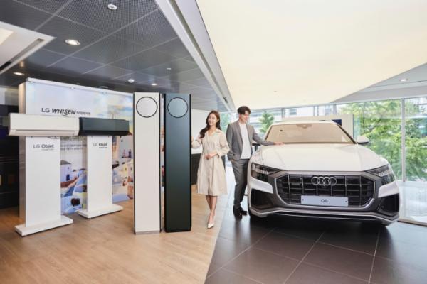 ▲LG전자가 독일 프리미엄 자동차 브랜드인 아우디(Audi)와 손잡고 휘센 타워 에어컨 공동 마케팅을 진행한다. 모델들이 아우디 국내 공식딜러인 고진모터스의 매장 가운데 서울시 강남구 소재 도산대로점에서 LG 휘센 타워 에어컨(사진 왼쪽)과 아우디 Q8 차량을 소개하고 있다. (사진제공=LG전자)