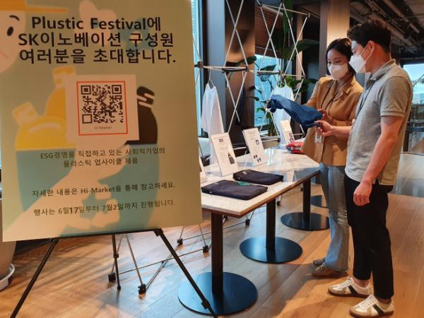 ▲SK이노베이션 계열 구성원들이 '플러스틱 페스티벌'에서 폐플라스틱을 재활용해 만든 제품들을 살펴보고 있다. (사진제공=SK이노베이션)