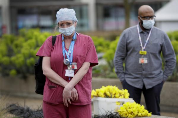 ▲영국 국민보건서비스(NHS) 소속 의료진이 3월 23일(현지시간) 런던의 한 병원 외부에서 묵념하고 있다. 런던/AP뉴시스