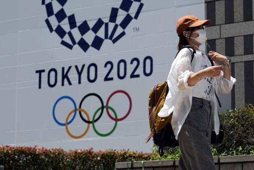 ▲2020 도쿄올림픽 현수막 앞을 마스크를 쓴 시민이 지나가고 있다. 도쿄/AP연합뉴스