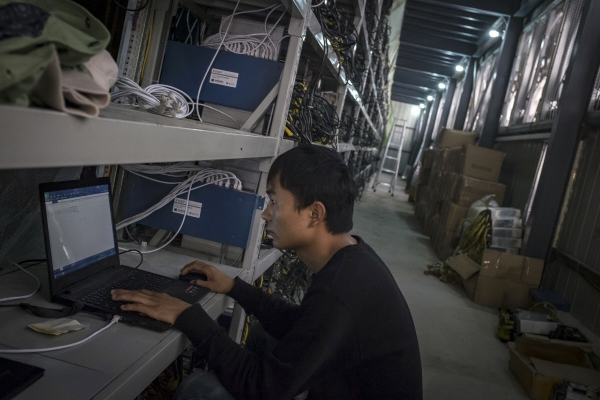 ▲2016년 9월 중국 쓰촨성 아바현의 한 수력발전소 인근에 있는 비트코인 채굴업체 직원이 채굴기계를 인터넷에 연결하는 작업을 하고 있다. 아바/AP뉴시스