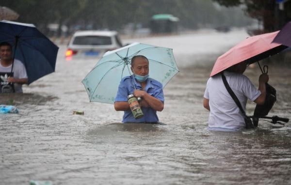 ▲중국 허난성 정저우에서 지난달 21일 한 남성이 홍수가 난 지역의 일대를 걷고 있다. 정저우/로이터연합뉴스
