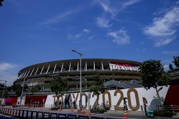 ▲도쿄올림픽·패럴림픽 개막식이 열리는 국립경기장 앞을 마스크를 쓴 사람들이 지나가고 있다. 도쿄/AP연합뉴스