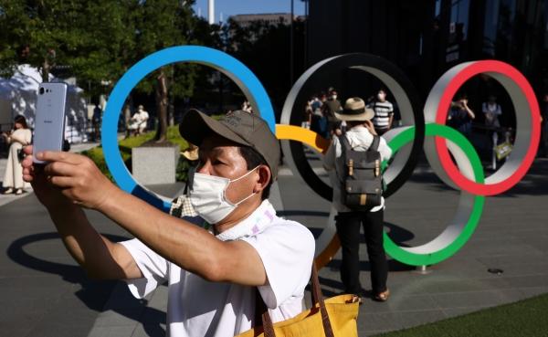 ▲일본 국립경기장 밖에 있는 올림픽 링을 배경으로 한 남성이 사진을 찍고 있다. 도쿄/타스연합뉴스