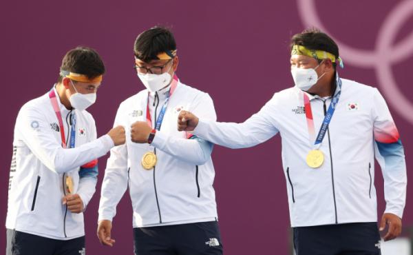 ▲김제덕(왼쪽부터), 김우진, 오진혁이 26일 유메노시마 공원 양궁장에서 열린 남자 단체전 시상식에서 금메달을 목에 걸고 주먹을 맞대며 기뻐하고 있다.