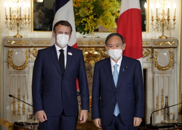 ▲스가 요시히데(오른쪽) 일본 총리가 지난 24일 일본 도쿄에서 에마뉘엘 마크롱 프랑스 대통령과 회담을 앞두고 포즈를 취하고 있다. 도쿄/EPA연합뉴스