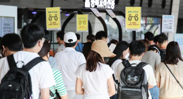 ▲30일 오전 서울 김포공항 국내선 청사에 거리두기 안내판 아래로 여행객들이 줄지어 서 있다. (연합뉴스)
