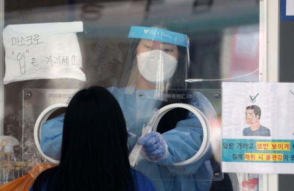 ▲코로나19 신규 확진자가 1,539명으로 집계, 25일째 네 자릿수를 기록한 지난달 31일 오전 서울 중구 서울역광장에 마련된 코로나19 중구임시선별검사소에서 의료진이 검체 채취를 하고 있다.  (뉴시스)