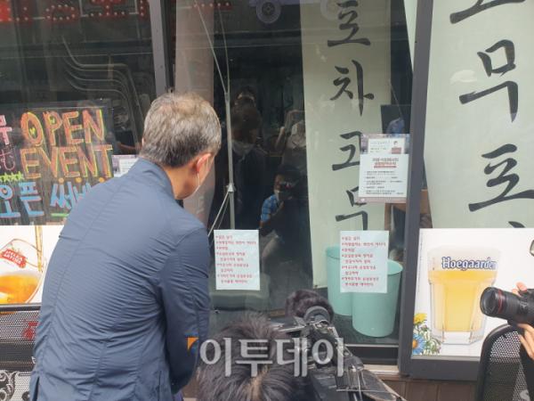 ▲최재형 대통령 선거 예비후보가 1일 오후 서울 용산구 이태원 세계음식문화거리를 방문해 휴업 중인 음식점 앞에 붙여진 문구를 읽고 있다. 해당 문구에는 '살고 싶다', '자영업자는 죄인이 아니다' 등의 내용이 적혔다. (박준상 기자 jooooon@)