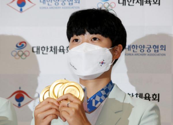 ▲2020 도쿄올림픽 양궁 3관왕 안산이 1일 귀국한 뒤 금메달 3개를 들어보이고 있다. (연합뉴스)