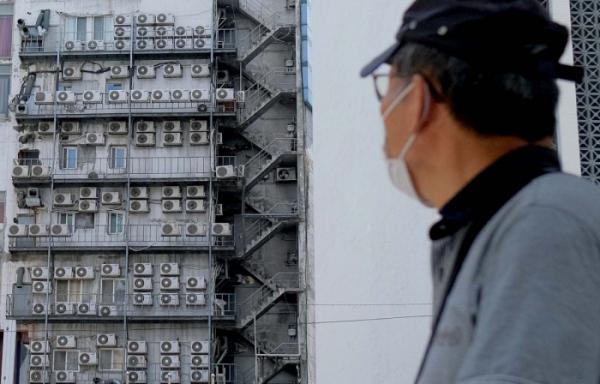 ▲서울 중구 한 건물 외벽에 설치된 에어컨 실외기를 한 행인이 바라 보고 있는 모습. (이투데이)