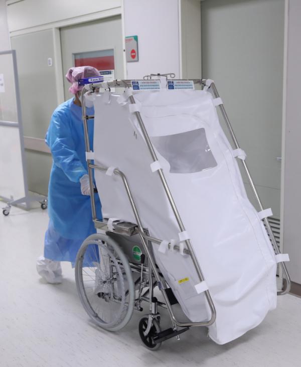 ▲13일 오전 국민건강보험 일산병원에서 간호사가 코로나19 확진 산모를 옮겼던 음압 휠체어를 다른 곳으로 옮기고 있다. (연합뉴스)