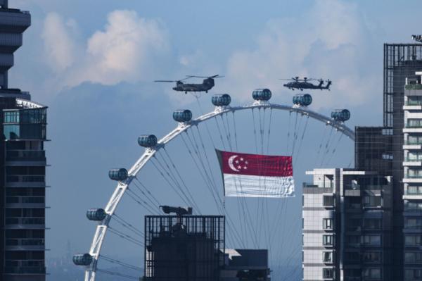 ▲9일 싱가포르의 독립기념일을 맞아 행사가 진행되고 있다. 싱가포르는 이틑날 코로나19 봉쇄 완화 조치를 발표했다.  (210809) -- SINGAPORE, Aug. 9, 2021 (Xinhua) -- Helicopters fly with Singapore's national flag during the National Day celebrations in Singapore, Aug. 9, 2021. Singapore celebrated the 56th anniversary of independence on Monday. (Xinhua/Then Chih Wey) (뉴시스)