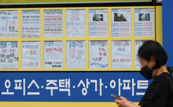 ▲한 시민이 서울 송파구 한 공인중개사에 붙은 매매 및 전세가격표를 지나치고 있다. (연합뉴스)