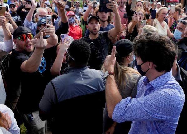 ▲쥐스탱 트뤼도 캐나다 총리가 6일(현지시간) 온타리오주 브랜포드에서 총선 유세를 벌이는 가운데 백신 의무 접종 반대 시위 참가자 일부가 손가락으로 욕설하자 엄지를 치켜세우고 있다. 브랜포드/로이터연합뉴스