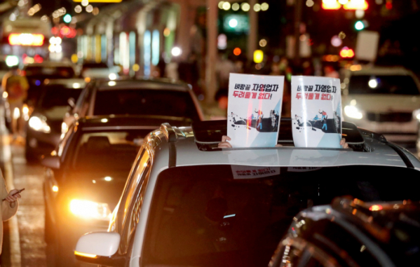 ▲전국자영업자비대위 회원들이 9일 새벽 서울 영등포구 여의대로에서 진행된 코로나19로 인한 고강도 사회적 거리두기 연장에 반발하는 전국동시차량시위에서 정부 방역지침을 규탄하는 손피켓을 들고 있다.  (뉴시스)