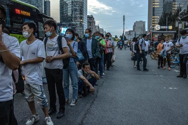 ▲중국 베이징에서 13일 시민들이 거리두기 없이 일렬로 서 버스를 기다리고 있다. 베이징/EPA연합뉴스