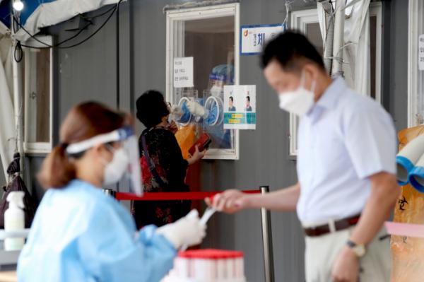 ▲코로나19 일일 신규 확진자 수가 3273명으로 집계돼 역대 최대치를 보인 25일 오전 서울 중구 서울역에 마련된 임시선별검사소에서 시민이 검사를 받고 있다. (뉴시스)