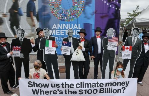 ▲국제통화기금(IMF)·세계은행(WB) 본사 앞에 놓인 세계 주요국 지도자들의 판넬 앞에서 활동가들이 시위를 벌이고 있다. 워싱턴D.C./로이터연합뉴스